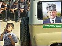 Boy stands by van adorned with poster of Akhmad Kadyrov