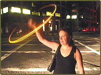A woman swings a light to hail a cab in the darkness of New York City following giant blackouts