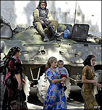 Russian soldier watches voters from an armed personnel carrier