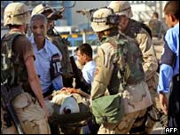 US soldiers and Iraqi police evacuate wounded people from the UN headquarters at the Canal Hotel  in Baghdad