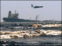 Plane flying low over sinking tanker