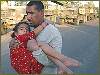 An injured girl is carried from the blast site at the UN headquarters at the Canal hotel in Baghdad
