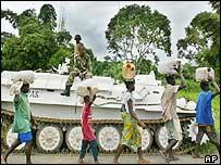 Civilians walk past a peacekeeping vehicle