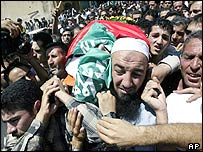 The flag-draped body of Mazen Dana is carried through Hebron's streets