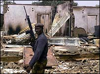 A Nigerian army soldier walks through a destroyed neighbourhood in Kaduna after clashes in 2000