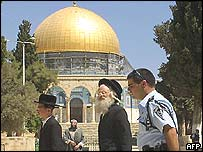 Two Orthodox Jews guarded by an Israeli policeman walk past the Dome of the Rock, 20 August