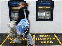 Woman walking past cash machines
