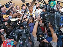 Kobe Bryant is surrounded by the media after training