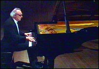 Alfred Brendel in evening jacket on stage