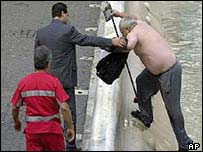 Previous suspect Roberto Cercelletta being removed from the fountain