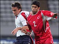 Turkey's Fatih Sonkaya, right, fights for the ball with David Prutton