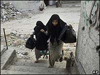 Palestinian women run away from a gunfight during an Israeli incursion in Rafah refugee camp