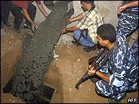 Palestinian policemen close a tunnel in the Rafah refugee camp, close to the Egyptian border