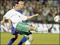 Northern Ireland defender Aaron Hughes gets the ball away from Greece's Stelios Giannakopoulos