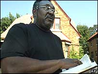Pastor David Hemphill with a copy of the Bible outside his home in Milwaukee