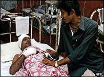 Gulam Hussain (L) is comforted by his relative Afzar Shakpur as he lies in a bed recovering from injuries