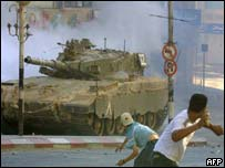 Palestinians throw stones at an Israeli tank during clashes in the West Bank city of Nablus