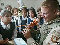 A US soldier distributes pencils in a girls' school