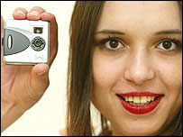 Tiny digital camera and smiling woman
