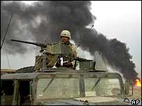 A US soldier secures the area near a fire fuelled by spent ammunition outside Sadr City