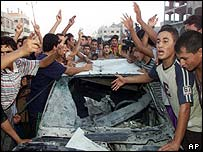 Palestinians with destroyed car