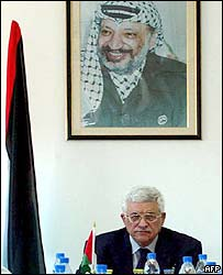 Abu Mazen chairing a cabinet meeting, with a portrait of Yasser Arafat above him