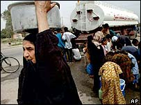Iraqi women receive water from a tanker