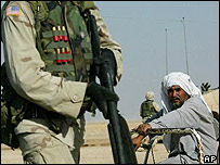 US soldier stands guard in front of Iraqi man