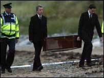 Garda officers accompany a coffin being removed from the beach
