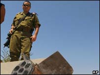 An Israeli soldier looks at the remains of Qassam rocket that landed in an open field near the industrial zone in Israeli the coastal city of Ashkelon