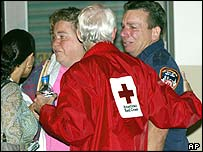 Red Cross worker assists a distraught man