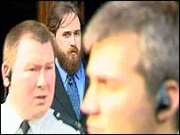 McArthur (bearded) leaves court flanked by police officers