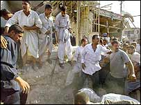 Men try to clear the blast site near the Shrine of Imam Ali