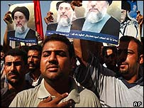 Iraqis protesting in Baghdad carry posters of Ayatollah Hakim