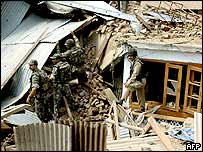 Indian soldiers search the debris of a destroyed house, Srinagar, 30 August 2003