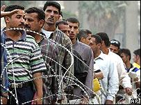 Unemployed Iraq men line up in central Baghdad to find work