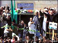 The coffin passes through the crowds in the streets of Kadhimiyah