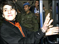 Kurdish dissident Leyla Zana shows her handcuffs as she gets into prison vehicle after appearing in court