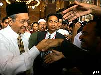 Mahathir Mohamad is greeted by well-wishers as he leaves the Putra mosque after Friday prayers, 17 October 2003