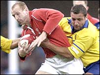 Gareth Thomas of Wales is tackled by Draos Dima