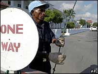 An East Timorese security guard at the U.N. headquarters opens its main gate in Dili, East Timor, Thursday, Oct. 2, 2003. A