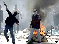 Arab demonstrators throw stones at police in Nazareth, 1 October 2000