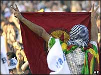 A Kurdish demonstrator unfurls a PKK banner at a peace rally