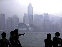 Several people gather along Hong Kong waterfront to watch the darkening sky