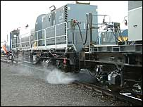 A train sprays the line to clear it of leaves