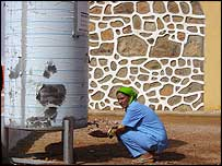 Woman getting water from a water tank
