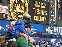 A man carries his child into Shea Stadium