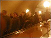 Люди спускаются вниз по эскалатору