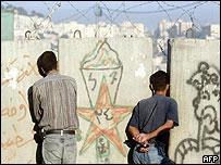Палестинцы смотрят на израильскую территорию сквозь щелки в стене