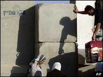 Palestinos trepan las piedras con las que Israel construye su muro de seguridad